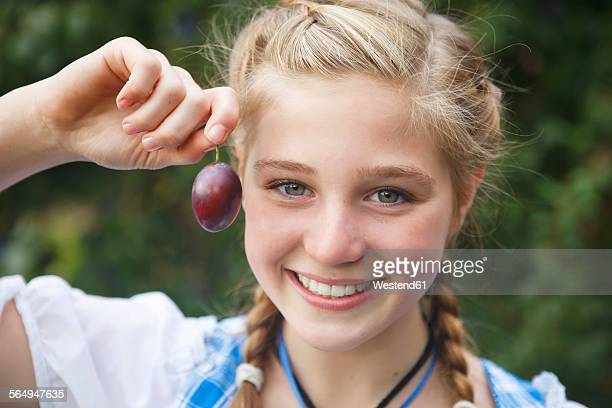 Germany, Luneburger Heide, portrait of smiling blond girl showing plum