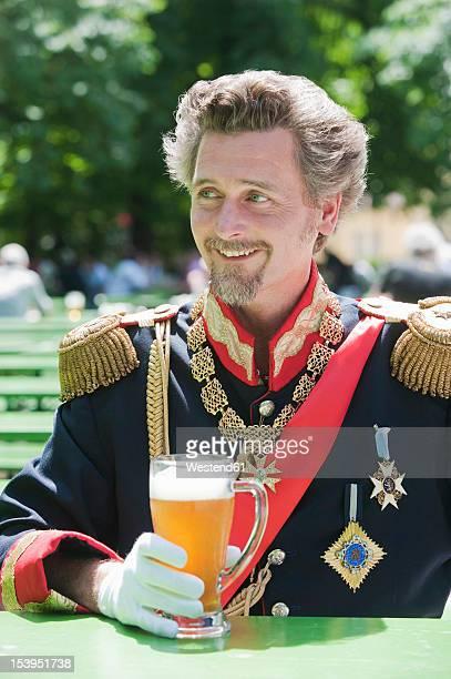 Germany, Man as King Ludwig of Bavaria with beer mug, smiling