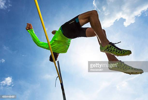 Germany, Man athlete jumping Hurdles on track