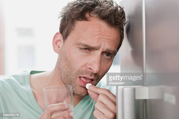 Germany, Man taking medicine, close up