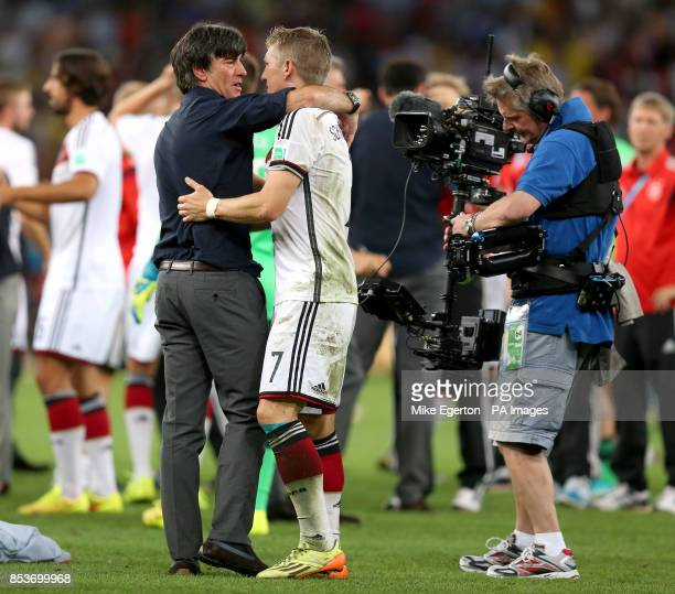 Germany manager Joachim Lowe celebrates victory with Germany's Bastian Schweinsteiger as a television cameraman films them after the FIFA World Cup...