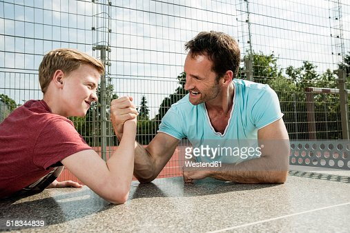 Germany, Mannheim, Father and son arm wrestling