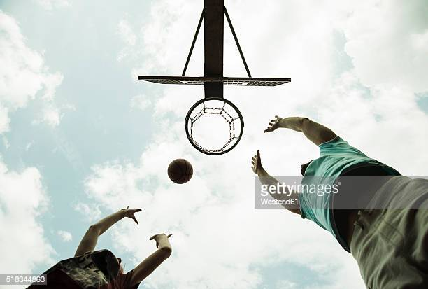 Germany, Mannheim, Father and son playing basket ball