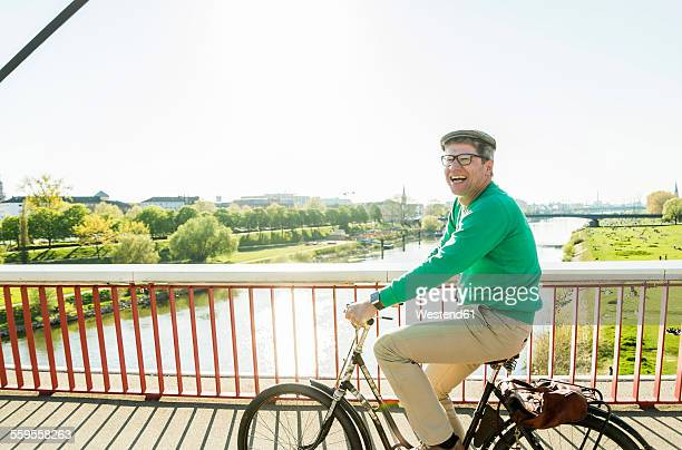 Germany, Mannheim, Mature man cycling over bridge