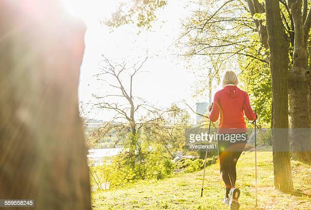 Germany, Mannheim, Mature woman Nordic walking in the park