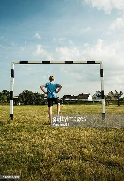 Germany, Mannheim, Teenage boy standing in goal, hands on hips