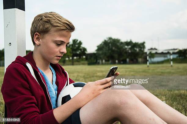 Germany, Mannheim, Teenage boy with soccer ball, using smartphone