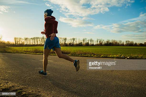 Germany, Mannheim, young man jogging on rural road