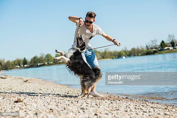 Germany, Mannheim, young man playing with dog at the riverside