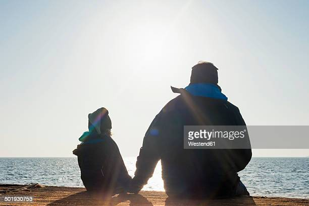 Germany, Mecklenburg-Western Pomerania, Ruegen, father and son looking at sea side by side