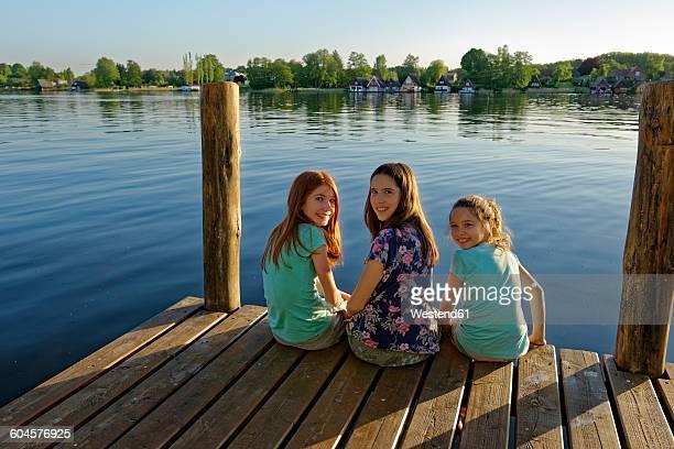 Germany, Mirow, three girls sitting on a jetty at Lake Mirow