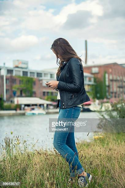 Germany, Muenster, young woman on a meadow near city harbour looking at her smartphone