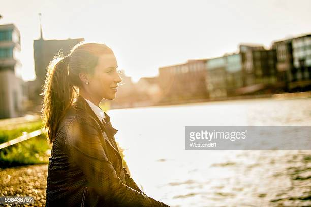 Germany, Muenster, young woman relaxing at city harbour in evening twilight