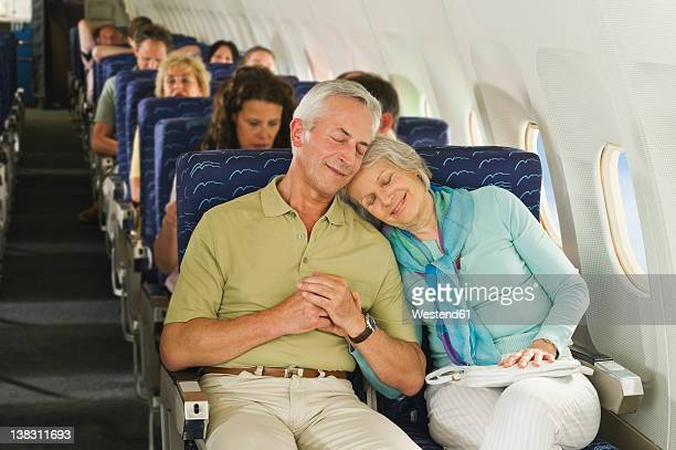 Germany, Munich, Bavaria, Group of passengers in economy class airliner, smiling