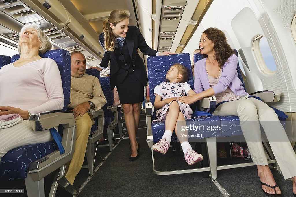 Germany, Munich, Bavaria, Passengers with stewardess in economy class airliner