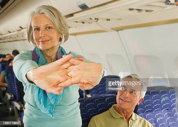 Germany, Munich, Bavaria, Senior woman stretching and man looking in economy class airliner