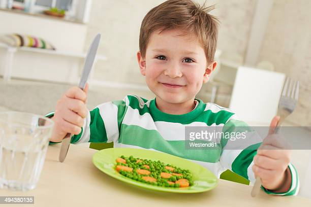 Germany, Munich , Boy eating peas and carrots