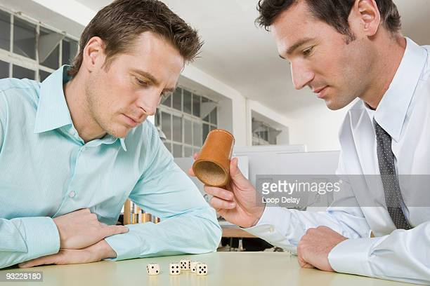 Germany, Munich, Two business men in office rolling dice, side view, portrait