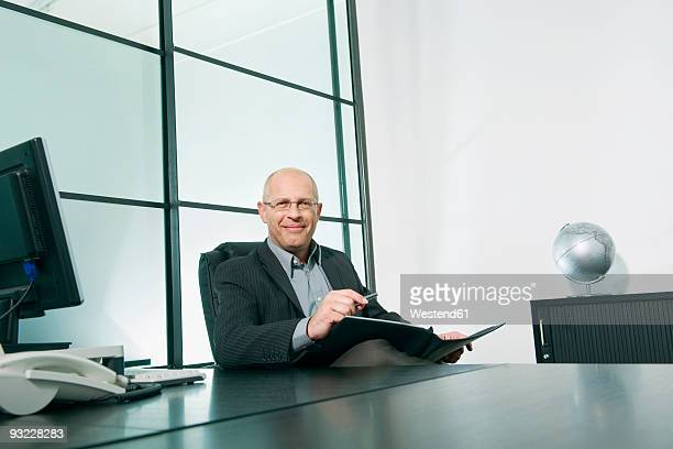 Germany, Munich, Businessman sitting in office, smiling, portrait