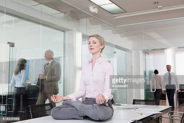 Germany, Munich, Businesswoman in office, meditating on desk