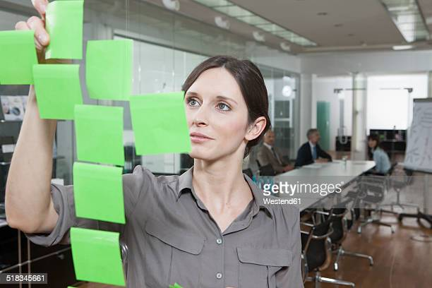 Germany, Munich, Businesswoman in office, putting sticky notes on glass pane