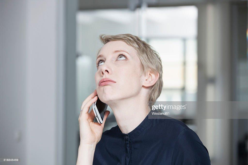 Germany, Munich, Businesswoman in office, using smart phone