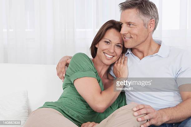 Germany, Munich, Couple sitting on couch, smiling
