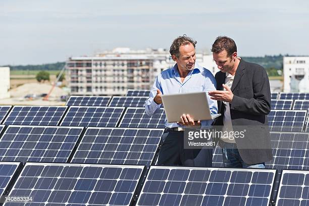 Germany, Munich, Engineer and man discussing in solar plant