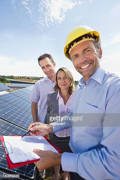Germany, Munich, Engineer with man and woman in solar plant, smiling, portrait