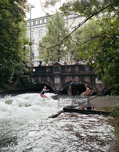 Germany, Munich, Englischer Garden, surfer riding Eisbach River wave