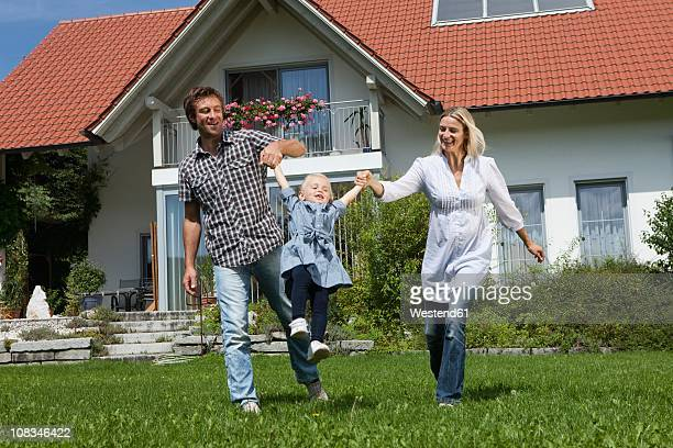 Germany, Munich, Family having fun in front of house