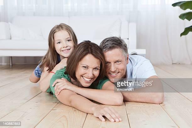 Germany, Munich, Family lying on floor, smiling, portrait