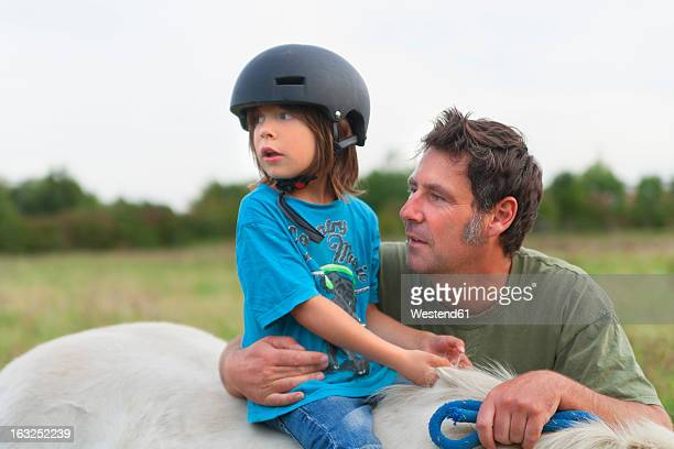 Germany, Munich, Father and son with horse in children's camp