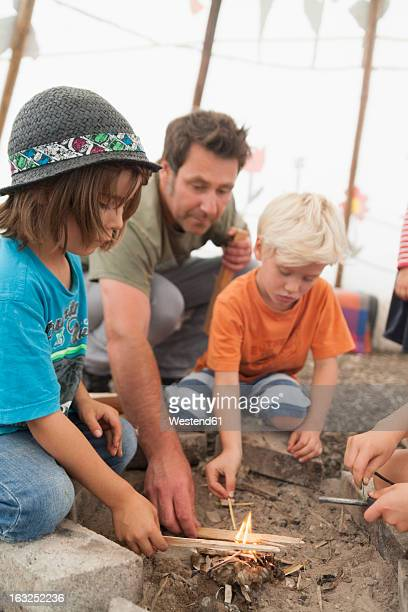 Germany, Munich, Father with children preparing camp fire in tent