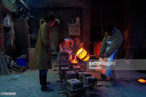 Germany, Munich, Foundry worker pouring hot metal into cast