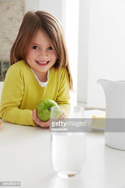 Germany, Munich, Girl sitting at table with green apple