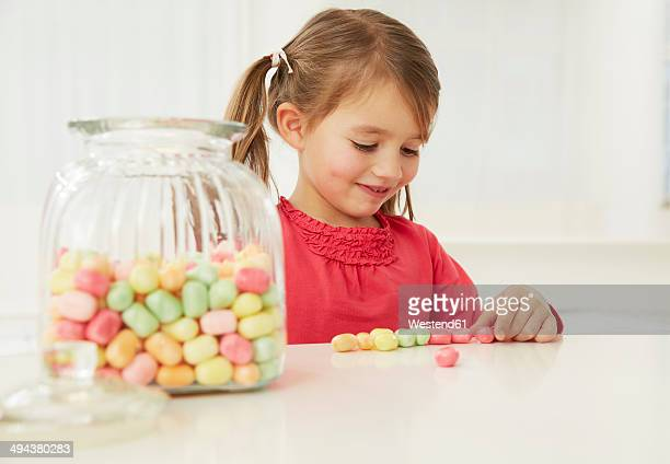 Germany, Munich, Girl with candy jar, counting candies