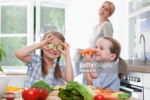 Germany, Munich, Girls (4-7) playing with vegetables in kitchen, mother standing in background : Stock Photo