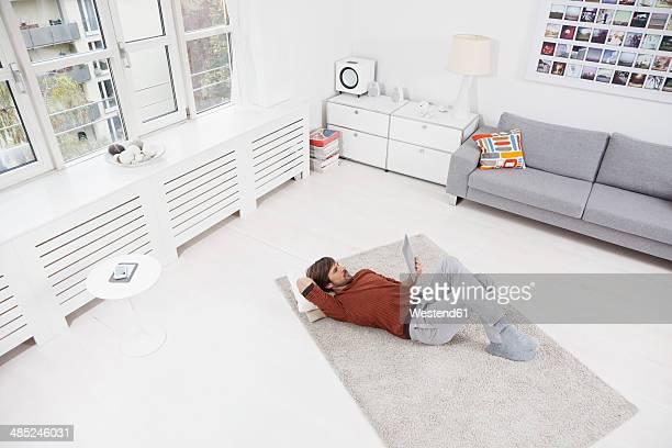 Germany, Munich, Man lying on floor, using, digital tablet