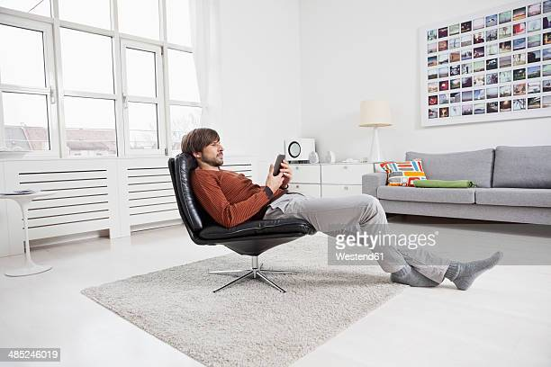 Germany, Munich, man reading e-book
