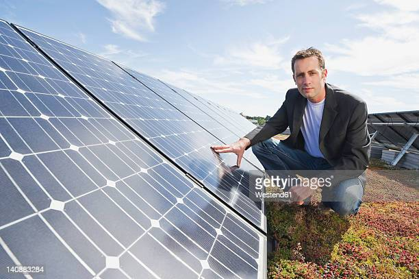 Germany, Munich, Man touching solar panel in solar plant, smiling, portrait