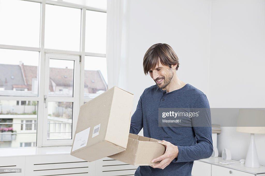 Germany, Munich, Man unpacking cardboard box