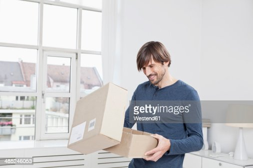Germany, Munich, Man unpacking cardboard box