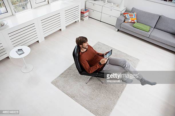 Germany, Munich, Man using digital tablet, sitting in chair
