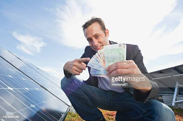 Germany, Munich, Man with euro notes in solar plant, smiling, portrait