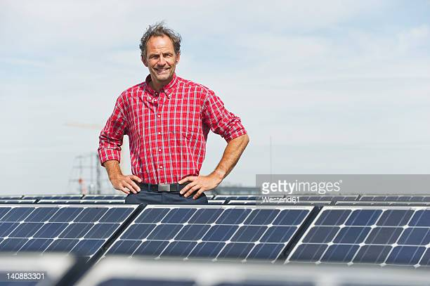 Germany, Munich, Mature man standing in solar plant, smiling, portrait