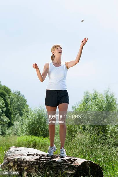 Germany, Munich, Mid adult woman juggling with stone on tree log, smiling