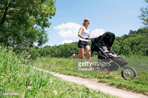 Germany, Munich, Mother jogging with baby boy in pram, smiling