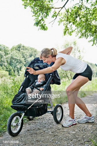 Germany, Munich, Mother with baby boy for jogging, smiling