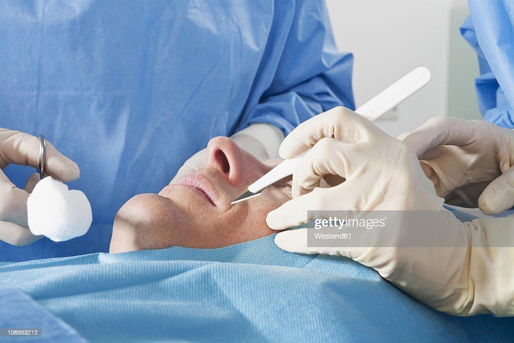 Germany, Munich, Surgeons performing operation : Stock Photo